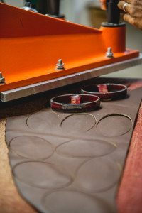 Clicking out S.B. Foot leather ovals for Frost River logos. After this step, the leather goes through several more passes, yielding smaller and smaller pieces until the leather scrap is minimal and no longer usable.