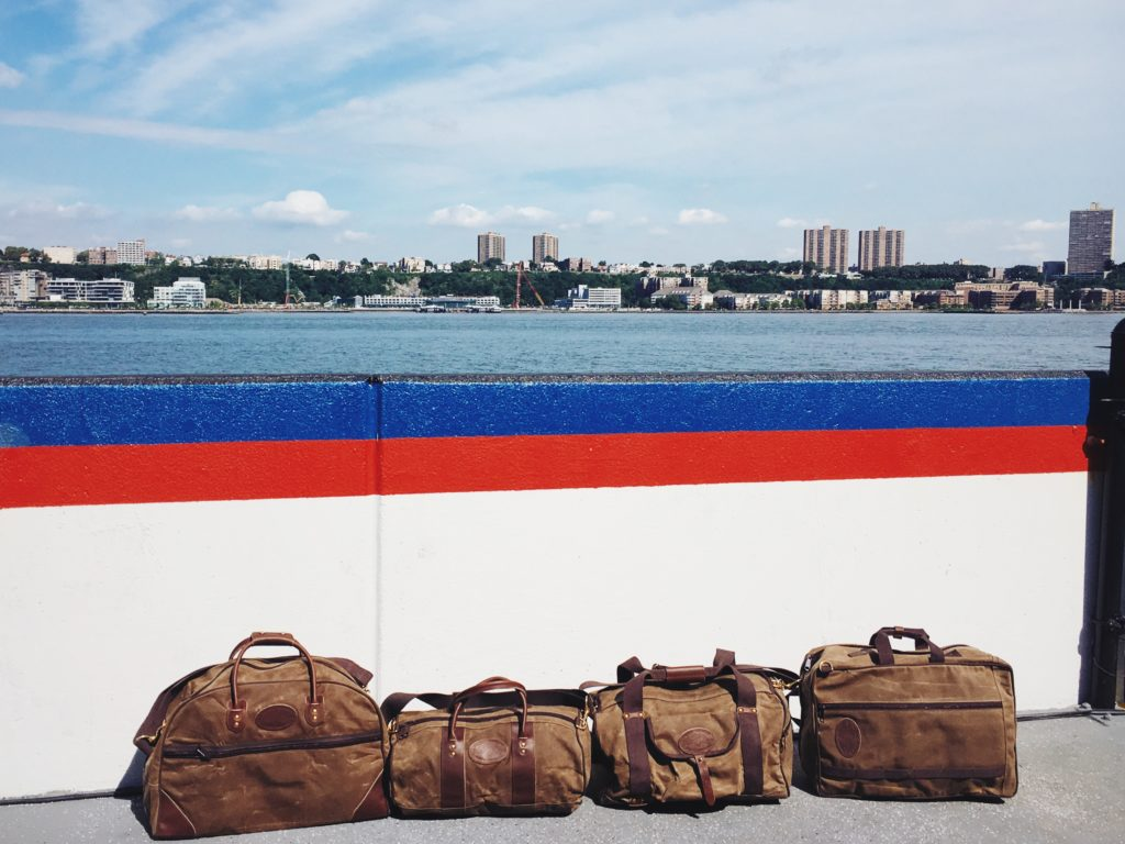 The Frost River Medium Curtis Flight Bag, Small Imout Round Duffel, Explorer ESB Carryon and Voyageur Backpack Brief on the pier in New York City. Luggage to the left, and two crossover luggage pieces to the right that are at home on a back or over a shoulder, these are versatile made-in-isa travelers.